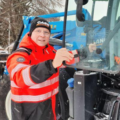 Mies on nousemassa traktoriin