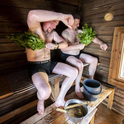 Två män använder bastukvastar.