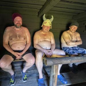 Kolme miestä savusaunan lauteilla.