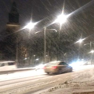Bilar kör i snöyra och förbi Åbo domkyrka och höga snövallar.