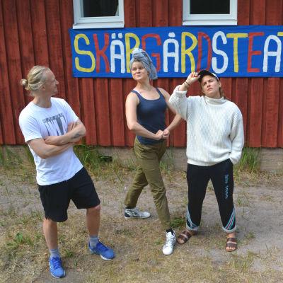 En ung man och två unga kvinnor poserar framför en rödmålad vägg med banderollen skärgårdsteatern.