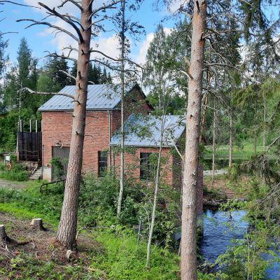Punatiilinen voimalaitosrakennus metsän siimeksessä