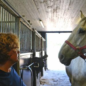 Kvinna och häst i stall ser på varandra