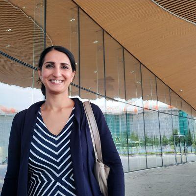 Kvinna tittar rakt in i kameran och står framför centrumbiblioteket Ode.