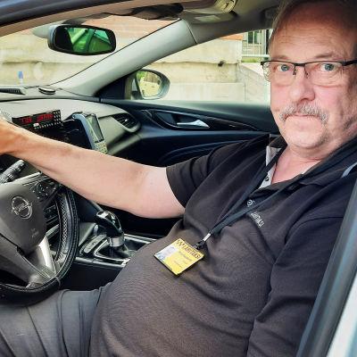 Äldre man med mustasch och glasögon som sitter bakom ratten i en bil.