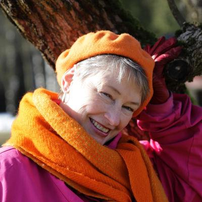 Oranssiin ja pinkkiin pukeutunut nainen lähikuvassa nojaamassa puunoksaan.