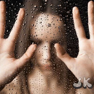 Flicka med händerna mot regnig vindruta.