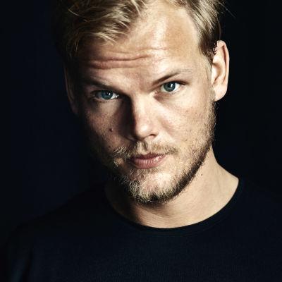 Edesmennyt ruotsalais-dj ja musiikkituottaja Avicii katsoo suoraan kameraan. Musta tausta.
