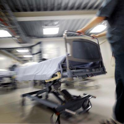 Sairaanhoitaja työtää sairaalasänkyä vuodeosaston käytävällä.