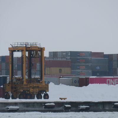 Mussalon satamassa lastauskone liikkuu konttien seassa.