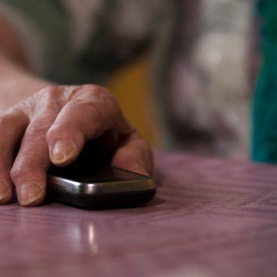 Vanhus kännykkä kädessä.