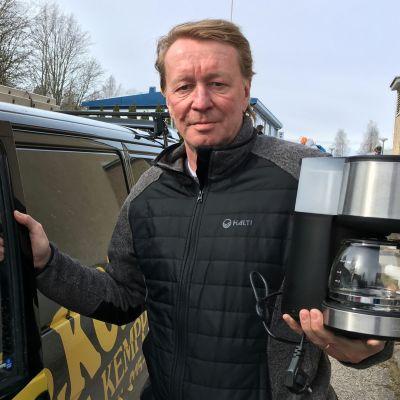 Tenho Kemppinen auton vierellä kahvinkeittimen kanssa.