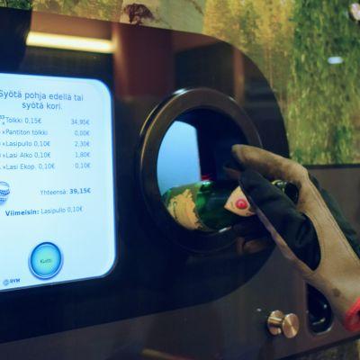 David Stephensin käsi laittamassa pulloa palautusautomaattiin. Automaatin näyttö kertoo, että hän on palauttanut pulloja yli kaksi sataa ja rajaa on melkein 40 euroa.