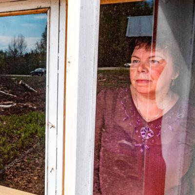 Tuija Rautiainen katsoo entisen kotinsa ikkunasta.