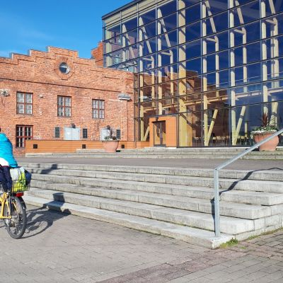 Pyöräilijä ajaa rakennuksen ohi