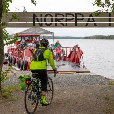 Pyöräilijä menossa Norppa II-lautan kyytiin