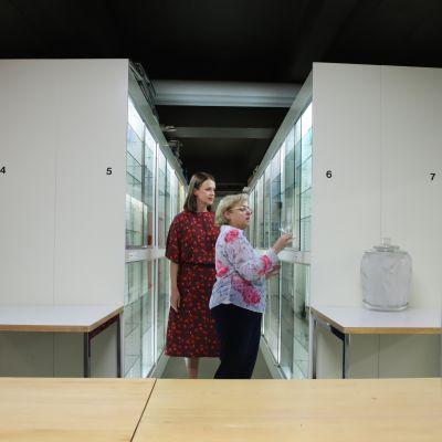 Kaksi naistaa tutkii lasimuseon varaston vitreenejä