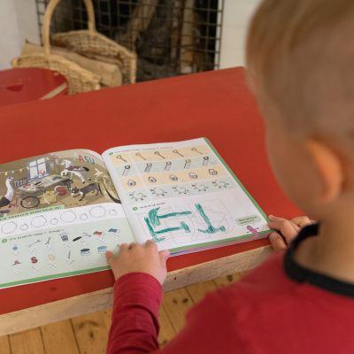 Poika katselee eskarikirjaa.