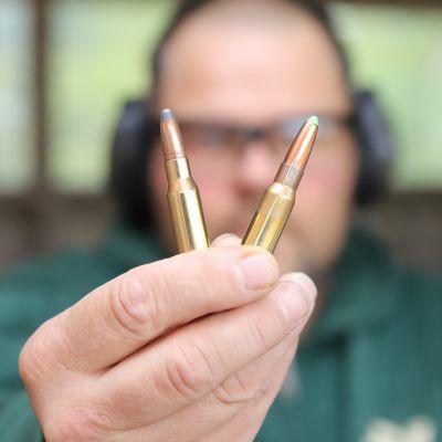 Mies esittelee kiväärinpatruunoita.