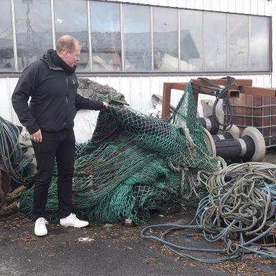 Mies seisoo kalastusverkkokasan vierellä.