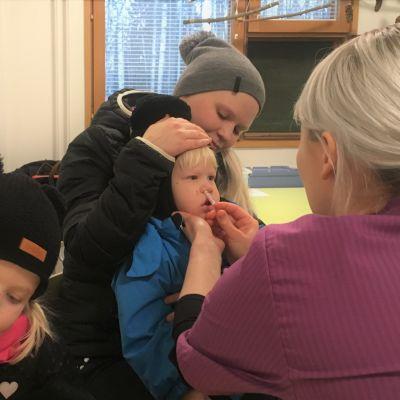 Perttu Hirvonen saa influenssarokotteen äitinsä Emmi Hirvosen sylissä. Pinja Hirvonen odottaa vuoroaan.