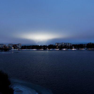 Urheilukentän valot heijastuvat kaupungin yllä oleviin pilviin.