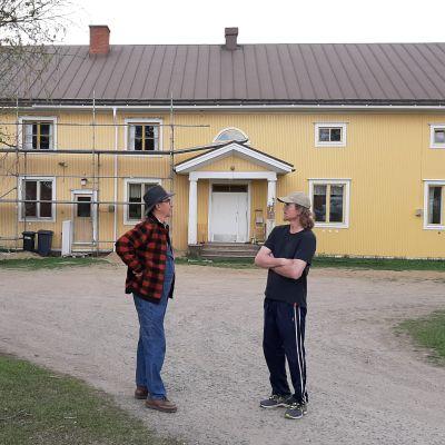 Kaksi miestä seisovat kylätalon pihalla.