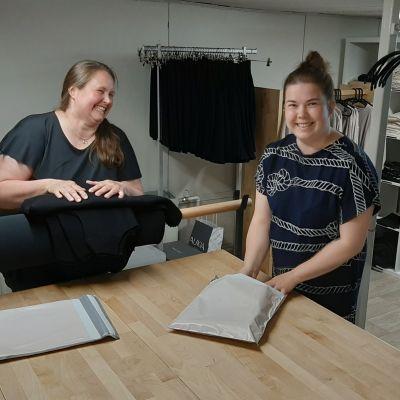 Kaksi naista viikkaavat vaatteita.