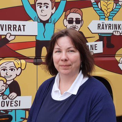 Nainen seisoo linja-auton vieressä.
