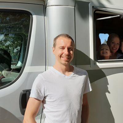 Mies ja lapset asuntoautossa.