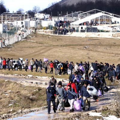 Siirtolaiset jättävät palavan leirin Bosniassa.