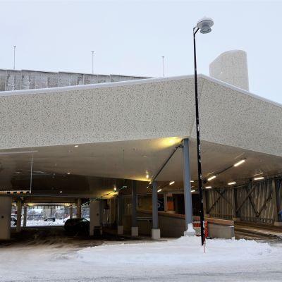 Uutukaisen asemaparkin sisäänajoluiska Joensuussa. Rakennuksen ensimmäisen kerroksen kautta kulkee myös saattoliikenne junille ja busseille.