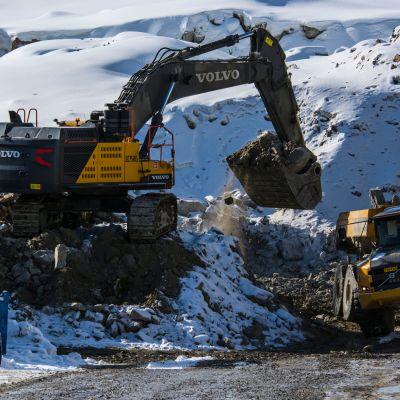 Kaivuri lastaa malmia dumperin kyytiin talvisella kaivoksella.