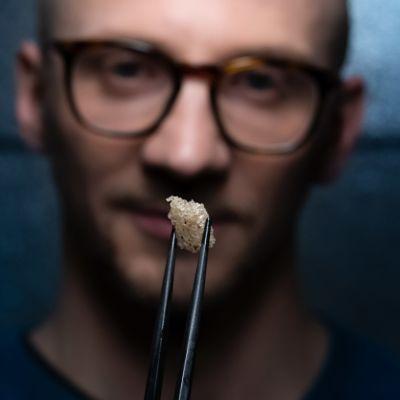 Lauri Reuter tutkii kasvisolukkoa syömäpuikkojen päässä.