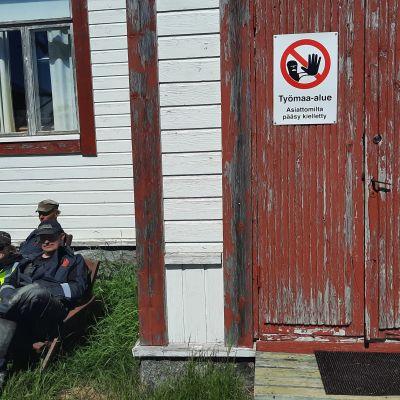 Seppo Salmi, Marko Asell ja Anna Patajoki istuvat nurmella talon edessä