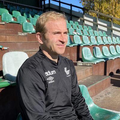 FC Lahden jalkapalloilija, kapteeni Kari Arkivuo istuu Kisapuiston jalkapallokentän katsomossa. Aurinkoinen sää pistää Karin silmät vähän siristämään.