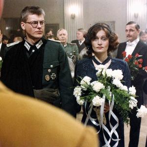 Häät sodan aikaan. Hääparina Tom Wentzel ja Irina Milan, taustalla Hannu Lauri. Elokuvasta Pedon merkki (1981)