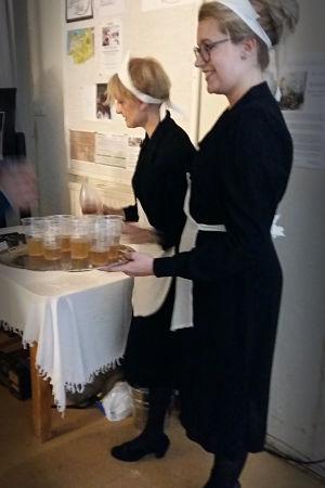 Två kvinnor klädda i servitrisuniform serverar drycker.