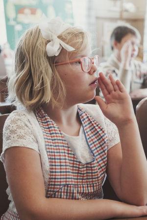 Skolbarn klädd i rosett och rutigt förkläde håller upp handen för att markera att hon kan rätt svar.