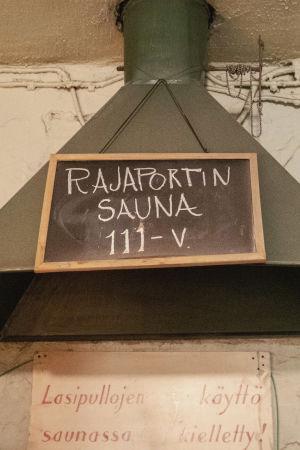 Rajaportin sauna 111-vuotta -kyltti roikkuu hormissa.