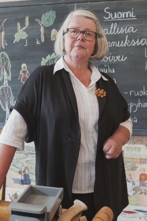 Dam i vit skjorta, svart kofta och glasögon står bakom en kateder, i bakgrunden svart tavla med teckningar och texter skrivna med krita.