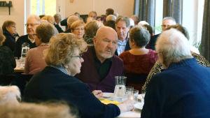 Äldre människor samtalar vid bord.