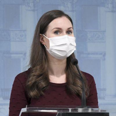 Statsminister Sanna Marin talar vid ett talarpodium. Hon har munskydd på sig.
