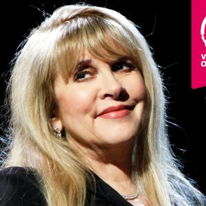 Stevie Nicks ler vid en mikrofon.