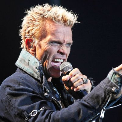 Billy Idol sjunger i en mikrofon och pekar med andra handen.