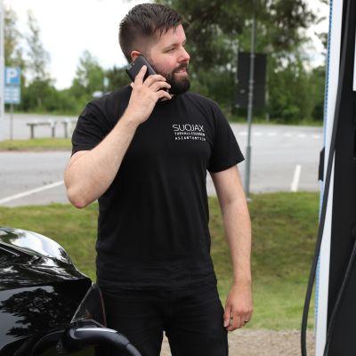 Miea puhuu puhelimeen ja lataa sähköautoaan