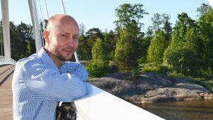 Tomas Palmgren lutar mot broräcke. I bakgrunden lummiga träd.
