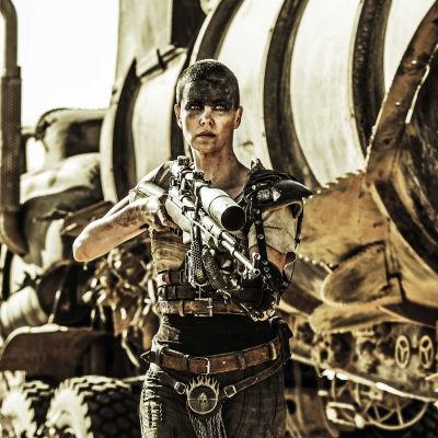 Furiosa (Charlize Theron) kommer gående mot kameran med ett stort vapen i händerna.