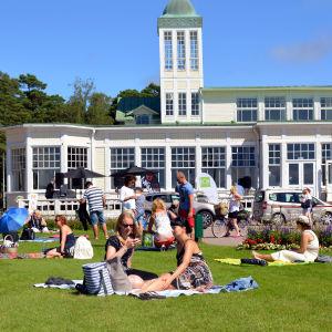 Människor sitter framför Hangö Casino och har picknick.