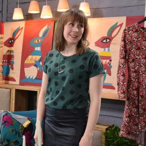 En kvinna, Anna-Karin Pörtfors som syr det mesta hon äger av återvunna tyger. Här iklädd en grön t-skjorta med svarta prickar och en kort läderkjol som hon sytt själv.